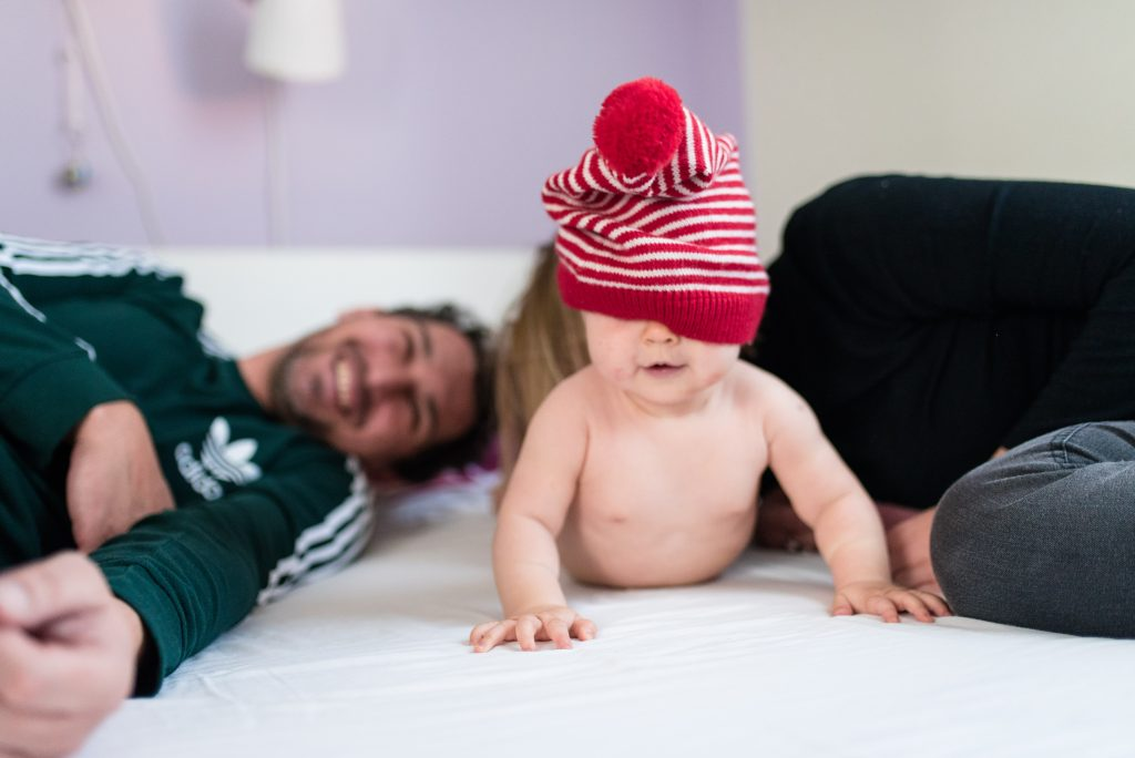 happy family parents laughing cute hat covering baby girls eyes