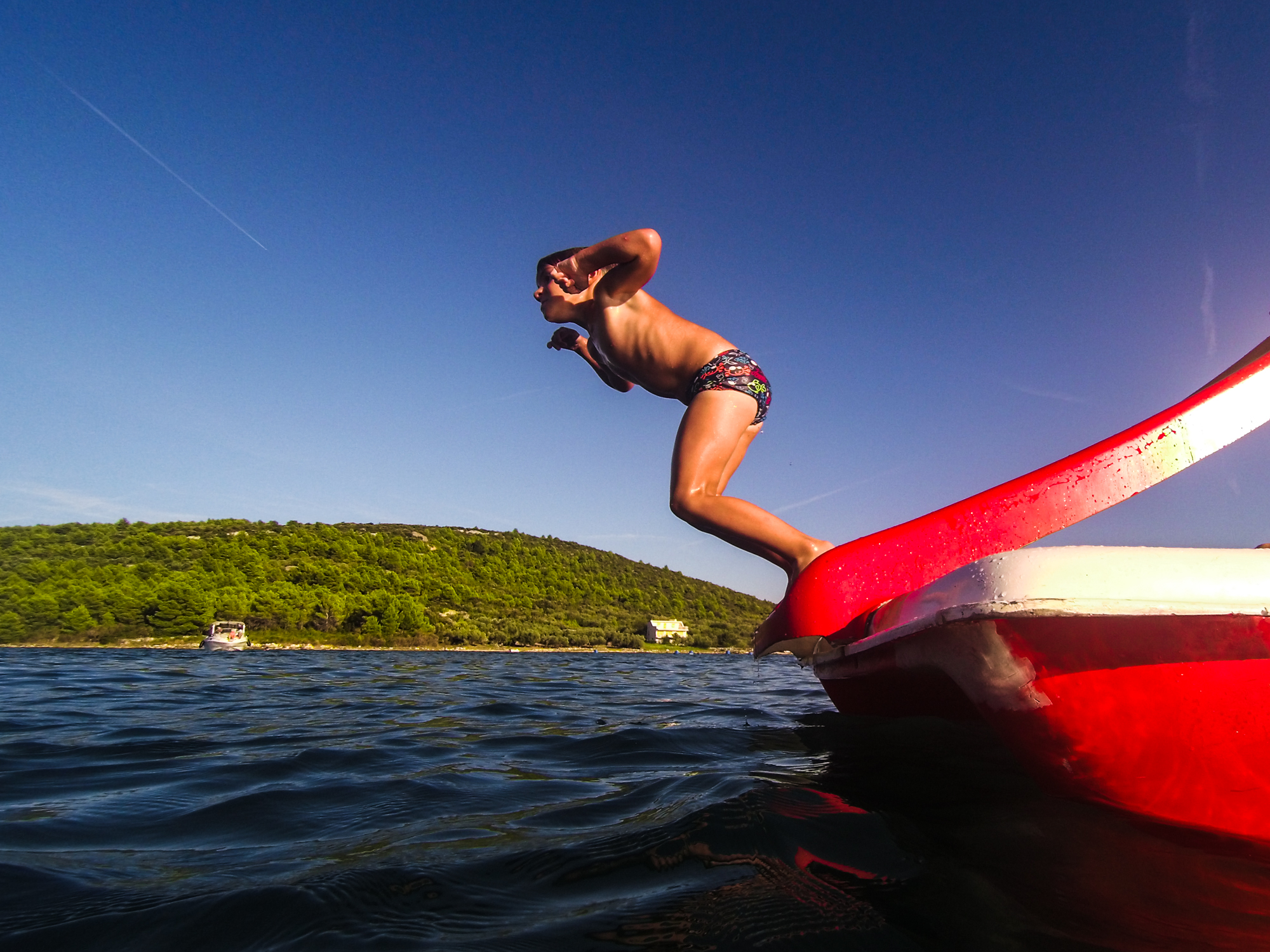 boy jumping into the sea from a red paddle boat Croatia
