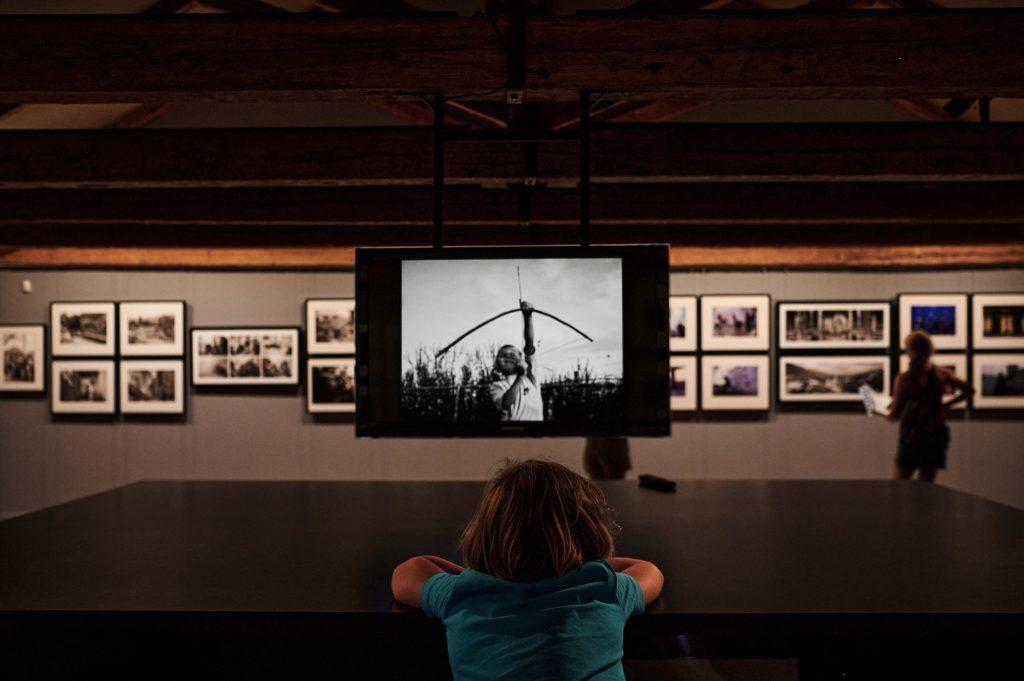 dječak gleda sliku dječaka rođenog za vrijeme rata u bosni i hercegovini. srebrenica. fotografija tarik samarah