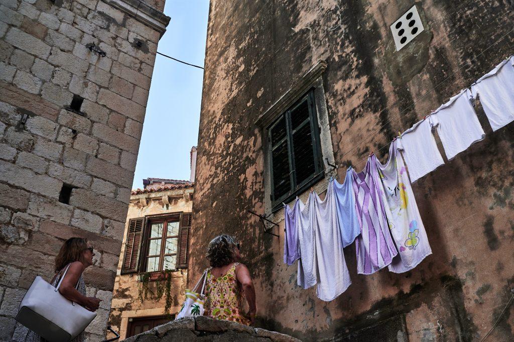 dvije gospođe gledaju robu obješenu na prozoru, dubrovnik, kolovoz 2020