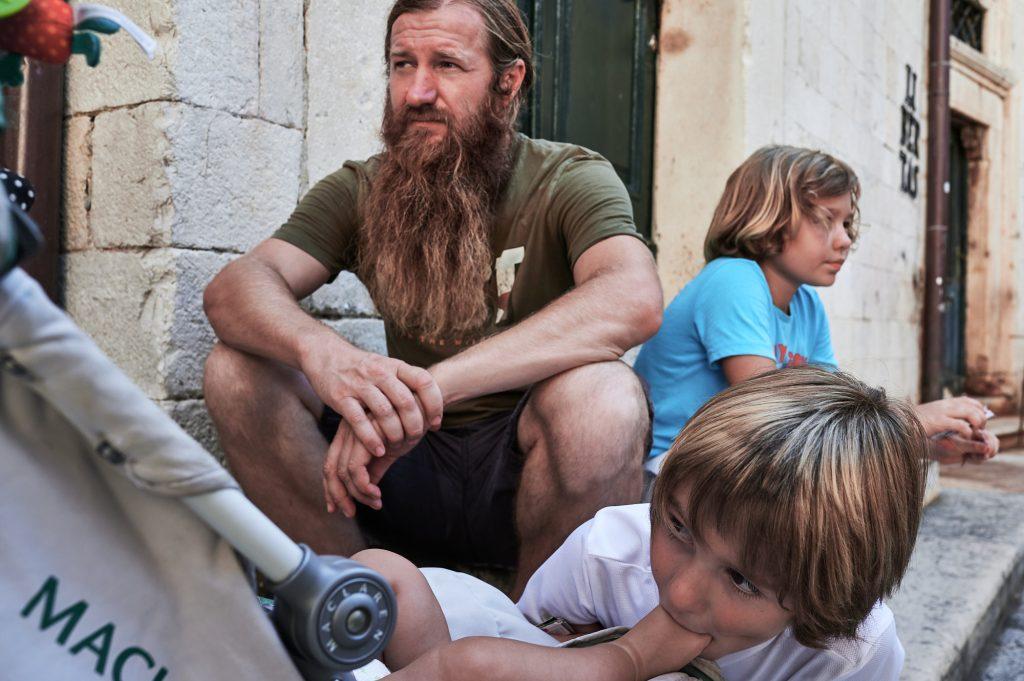 u pauzi od razgledavanja, otac s trojicom sinova, svatko radi svoj posao, dubrovnik, kolovoz 2020