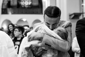 dad in church tenderly holding and kissing his boy