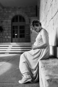 pregnant bride holding her tummy and talking to her child