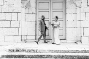 groom approaching bride in front of church doors black and white
