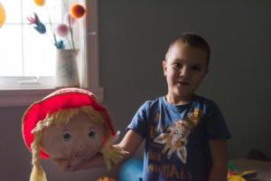 a boy showing cut head of his doll