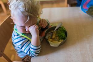 sleepy kid rubbing his eyes with hands fool of food